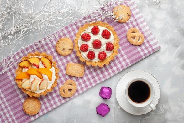 Vista de cima de bolos cremosos com creme branco saboroso e morangos fatiados, pêssegos, damascos com biscoitos e chá na mesa de luz, bolo de frutas assado com creme
