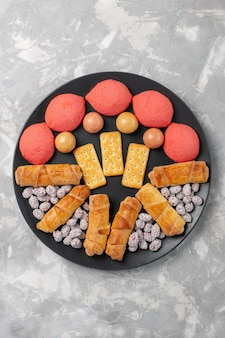 Vista de cima de bolos deliciosos com bagels e doces na mesa branca