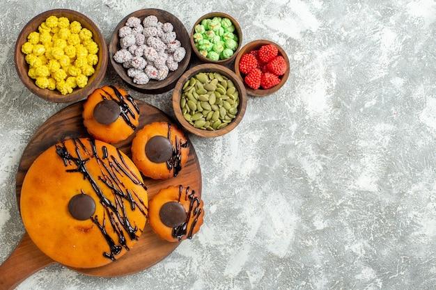 Vista de cima de bolos deliciosos com cobertura de chocolate e doces em um bolo de mesa branco torta de biscoito de cacau, sobremesa, biscoito doce