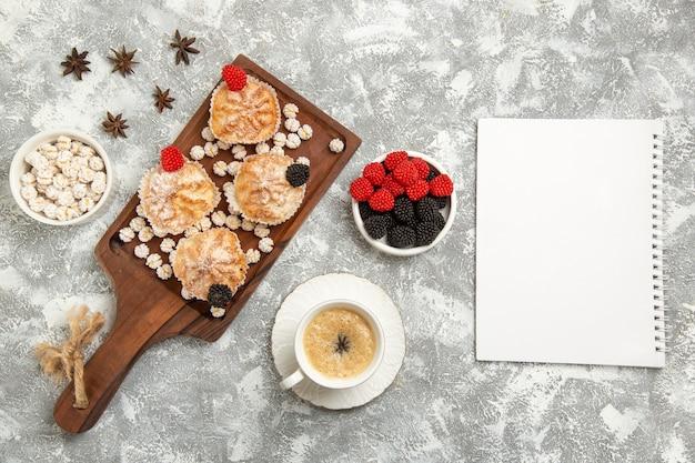 Vista de cima de bolos doces com balas e xícara de café na mesa branca