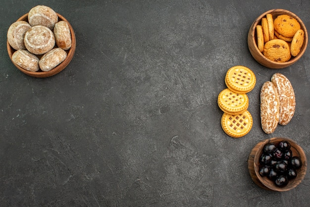 Vista de cima de bolos doces com biscoitos e azeitonas em um bolo de torta doce de superfície escura