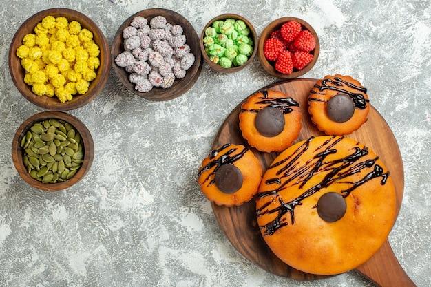 Vista de cima de bolos saborosos com cobertura de chocolate e doces na superfície branca bolo biscoito de cacau sobremesa biscoito doce