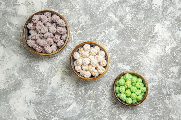 Vista de cima de bombons de açúcar dentro de pratinhos em um fundo branco claro.