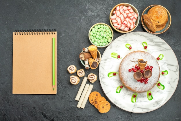 Vista de cima de cima de doces, um bolo com groselha, doces coloridos, waffles, lápis, caderno