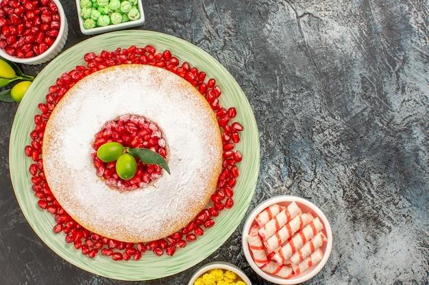 Vista de cima de cima de doces, um bolo com sementes de romã tigelas de doces coloridos na mesa