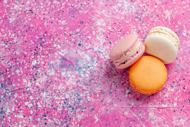 Vista de cima de cima, macarons franceses, deliciosos bolinhos na mesa rosa