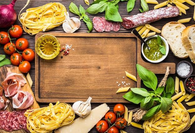 Vista de cima de comida tradicional italiana, aperitivos e lanches como salame, presunto, queijo, pesto, ciabatta, azeite de oliva, macarrão em uma placa de madeira rústica com espaço para texto