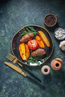 Vista de cima de costeletas de carne assadas com batatas e tomate, servidas com talheres verdes, temperos com alho e mistura de cores de fundo