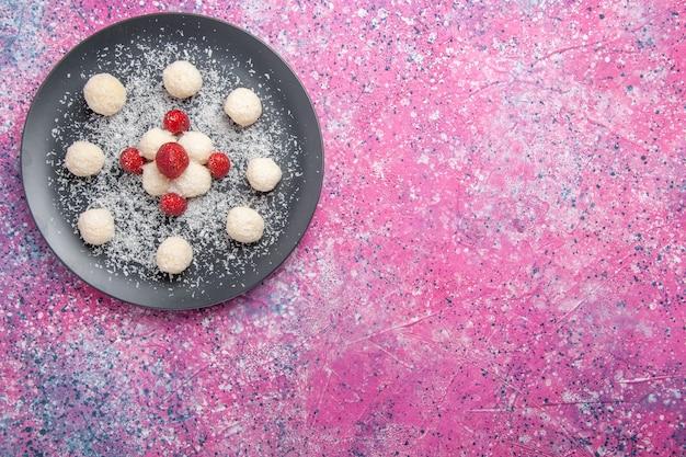 Vista de cima de deliciosas bolas de doces de coco no chão rosa.