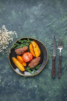 Vista de cima de deliciosas costeletas de carne assadas com batatas e tomates em um prato preto talheres com flores brancas sobre fundo verde preto de cores misturadas