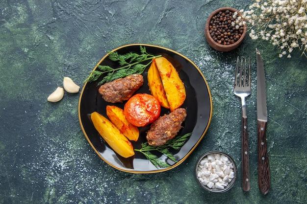 Vista de cima de deliciosas costeletas de carne assadas com batatas e tomates em uma placa preta talheres de especiarias de alhos em um fundo de cores preto e verde