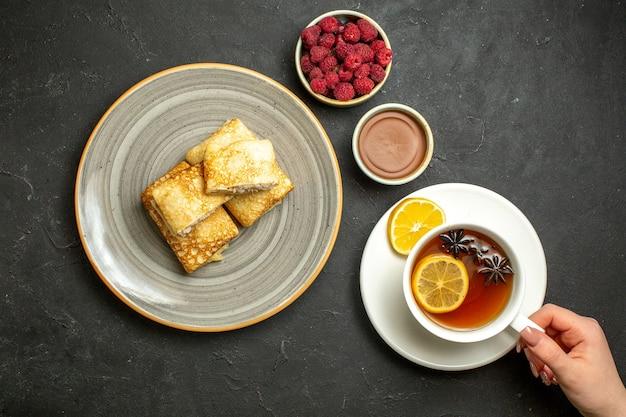 Vista de cima de deliciosas panquecas frescas em um prato branco e uma xícara de chá preto com acessórios de decoração de framboesa de chocolate em fundo escuro
