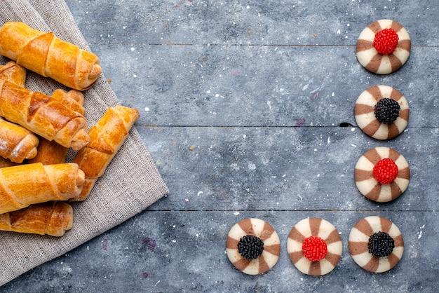 Vista de cima de deliciosas pulseiras formadas com recheio junto com biscoitos de chocolate em um chá cinza, biscoito doce doce com açúcar