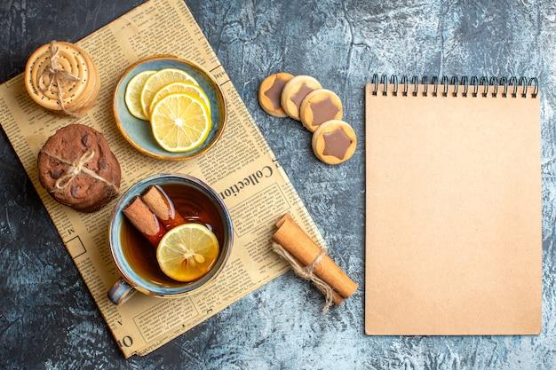 Vista de cima de deliciosos biscoitos e uma xícara de chá preto com canela em um jornal velho ao lado do caderno em espiral em fundo escuro