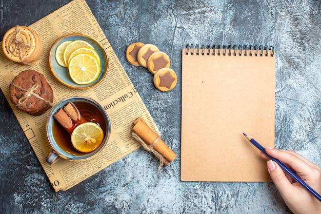 Vista de cima de deliciosos biscoitos e uma xícara de chá preto com canela em um velho jornal e segurando a caneta no caderno espiral em fundo escuro