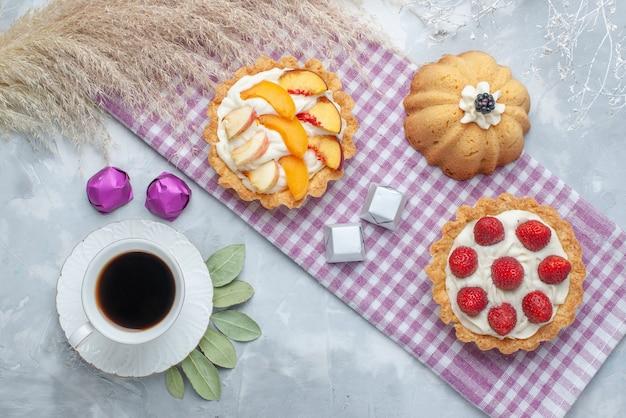 Vista de cima de deliciosos bolos cremosos com frutas fatiadas junto com bombons de chocolate e chá no chão claro bolo biscoito doce creme asse chá açúcar