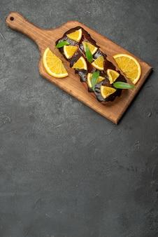 Vista de cima de deliciosos bolos decorados com laranja e chocolate na tábua de cortar na mesa preta