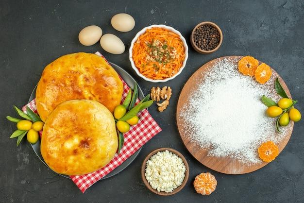 Vista de cima de deliciosos bolos frescos e queijo, pimentas, ovos, farinha, tangerinas, na tábua de madeira, salada