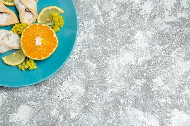 Vista de cima de deliciosos pastéis de massa com rodelas de limão em uma superfície branca clara