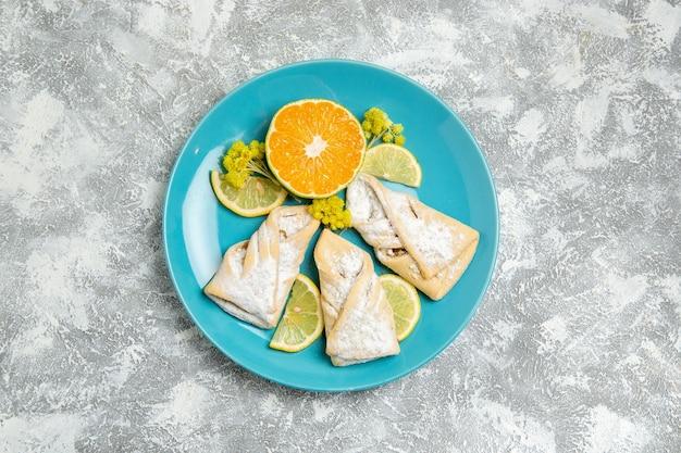Vista de cima de deliciosos pastéis de massa com rodelas de limão na superfície branca
