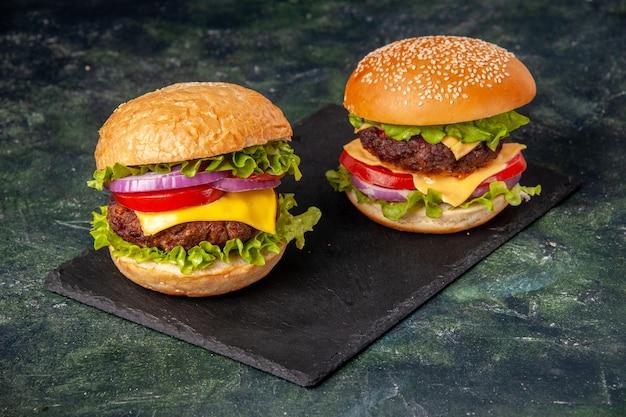 Vista de cima de deliciosos sanduíches caseiros no quadro negro na superfície cinza borrada