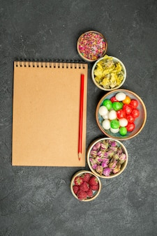 Vista de cima de diferentes doces coloridos em cinza de mesa cor do arco-íris açúcar doce