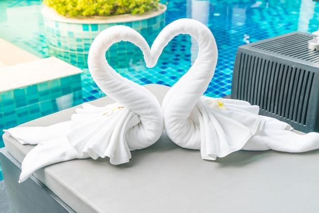 Vista de cima de duas lindas toalhas de cisnes na cama