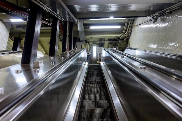Vista de cima de escadas rolantes de mão dupla com escada no metrô