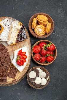 Vista de cima de fatias de bolo com biscoitos de frutas e barras de chocolate na mesa escura