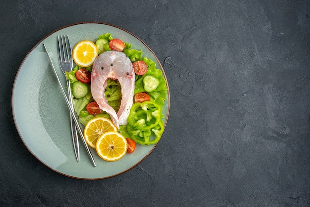 Vista de cima de fatias de limão e talheres de peixe cru e vegetais frescos em um prato cinza no lado esquerdo em uma superfície preta com espaço livre