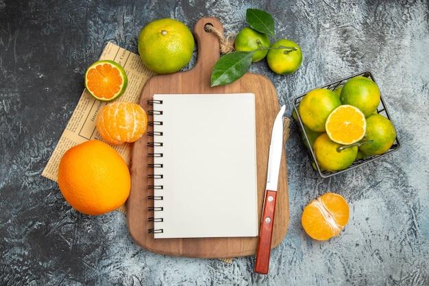 Vista de cima de frutas cítricas frescas com caderno de folhas em uma tábua de madeira cortada ao meio e uma faca em jornal em fundo cinza