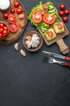 Vista de cima de legumes frescos inteiros cortados e especiarias na placa de madeira, talheres de toalha branca e conjunto de queijo na superfície preta