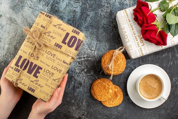 Vista de cima de lindas caixas de presente, rosas vermelhas, biscoitos empilhados, uma xícara de café no fundo escuro e gelado