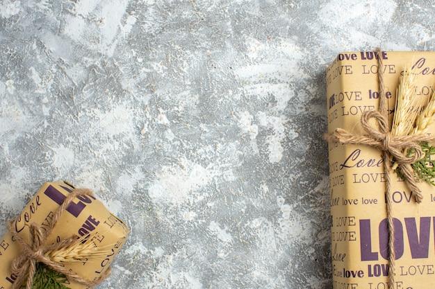 Vista de cima de lindos presentes de natal embalados, grandes e pequenos, com a inscrição de amor na superfície do gelo
