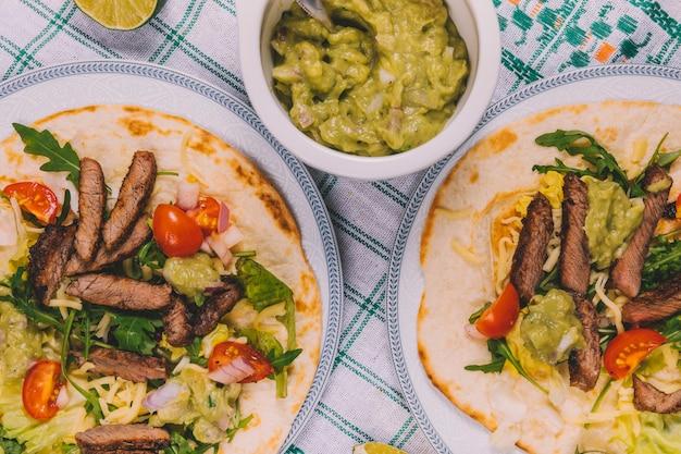 Vista de cima de listras de carne mexicana em tortilla com tigela de guacamole sobre toalha de mesa