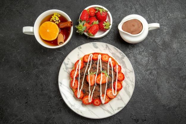 Vista de cima de longe bolo apetitoso uma xícara de chá com limão e canela ao lado das tigelas de morangos e creme de chocolate no centro da mesa