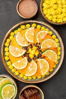 Vista de cima de longe bolo de doces com frutas cítricas e chocolate e tigelas de creme de chocolate bombons amarelos de chocolate e fatias de limão