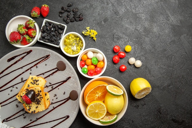 Vista de cima de longe bolo de frutas e frutas com morangos cobertos de chocolate ao lado de tigelas brancas de morangos, limas, limões, laranjas e doces coloridos na mesa