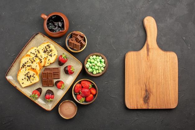 Vista de cima de longe bolo e bolo de chocolate e morangos cobertos de chocolate tigelas de morangos com chocolate, doces verdes e creme de chocolate ao lado da mesa da cozinha