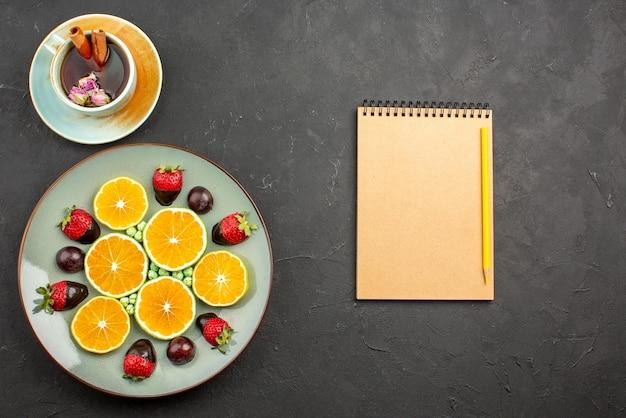 Vista de cima de longe chá com frutas com cobertura de chocolate morango apetitoso picado de laranja e balas verdes ao lado de uma xícara de chá com paus de canela ao lado de caderno de creme e lápis