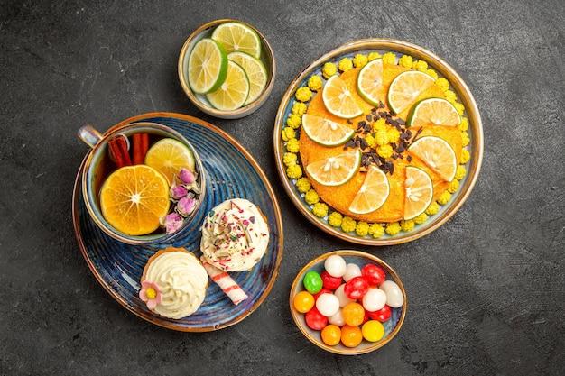 Vista de cima de longe chá de ervas azul pires com cupcakes e uma xícara de chá de ervas ao lado do prato de bolo com limas e tigelas de fatias de limão e doces na mesa preta