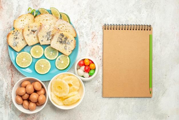 Vista de cima de longe com limão taças de pão de doces com ervas de limão no prato ao lado do caderno de creme e lápis sobre a mesa