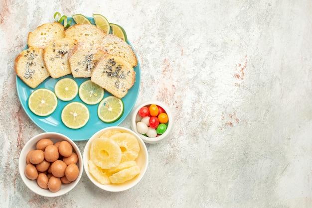 Vista de cima de longe com limão taças de pão doce com ervas de limão no prato sobre a mesa