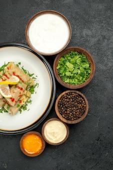Vista de cima de longe comida na mesa tigelas de pimenta preta creme azedo molho branco e amarelo e ervas e prato branco de repolho recheado com ervas limão e molho na mesa preta
