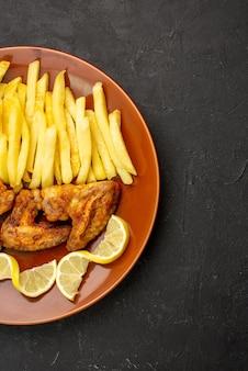 Vista de cima de longe, comida no prato, batatas fritas apetitosas, asas de frango e limão no lado esquerdo da mesa preta