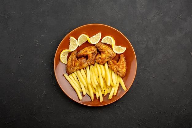 Vista de cima de longe comida no prato de asas de frango com batatas fritas e limão no prato laranja na mesa escura