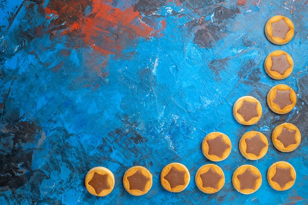 Vista de cima de longe doces biscoitos de chocolate na mesa azul
