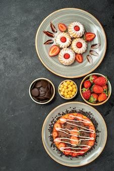 Vista de cima de longe, doces e bolo, biscoitos de morango e bolo com chocolate e tigelas de chocolate de noz de morango no lado direito da mesa preta