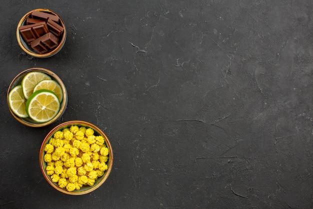 Vista de cima de longe doces tigelas de bombons de chocolate e fatias de limão no lado esquerdo da mesa