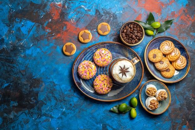 Vista de cima de longe doces uma xícara de café com biscoitos, grãos de café, frutas cítricas